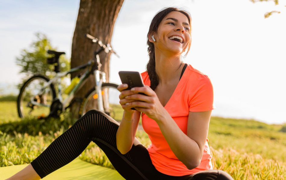 smiling-beautiful-woman-holding-phone-doing-sports-morning-park